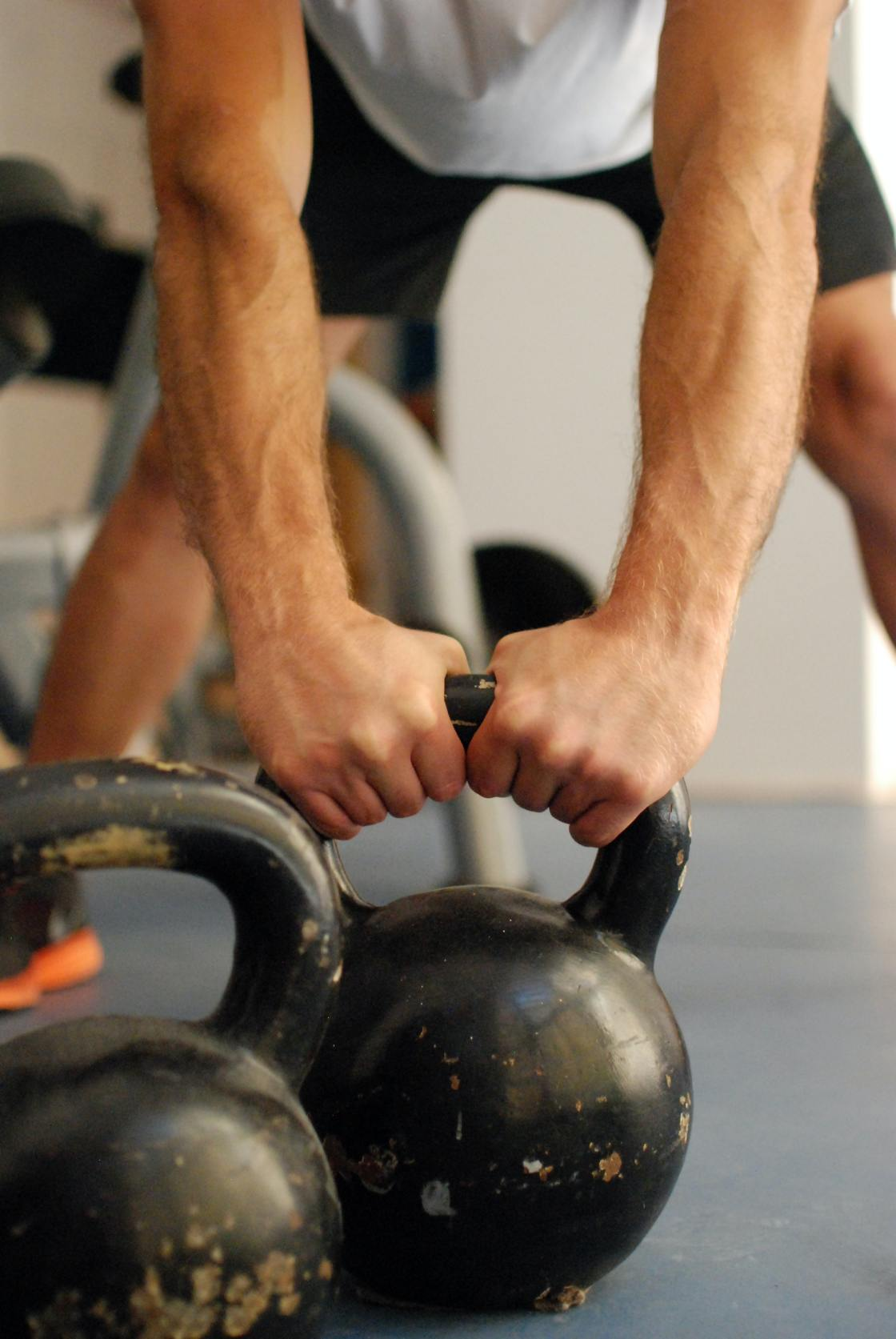 Man holding kettlebells as his workout helping him to get jacked